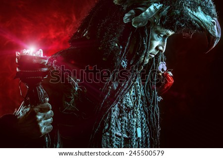 Portrait of a male shaman in ethnic dress surrounded by fog. Fantasy concept, magic. - stock photo