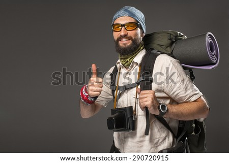 Portrait of a male smiling fully equipped tourist with backpack and the camera on gray background - stock photo