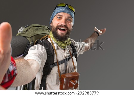 Portrait of a male smiling fully equipped tourist with backpack and the camera on gray background. tourist opened his arms, inviting travel - stock photo