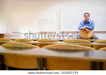 Portrait of a male teacher sitting on chair in the lecture hall - stock photo