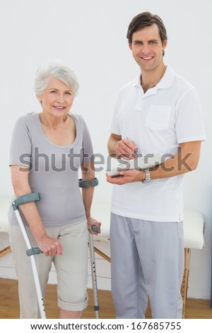 Portrait of a male therapist and disabled senior patient with reports in the gym at hospital - stock photo
