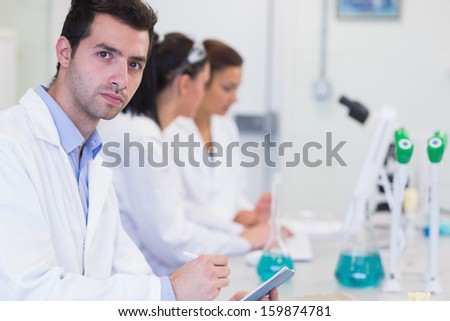 Portrait of a male with researchers working on experiments in the laboratory - stock photo