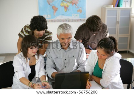 Portrait of a man and a group of teenagers in front of a laptop computer in a classroom - stock photo