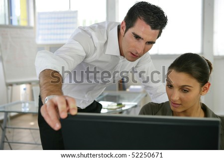 Portrait of a man and a woman in an office in front of a computer