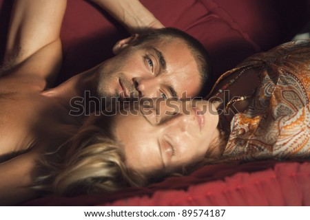 Portrait of a man and a woman laying down on a sofa. - stock photo