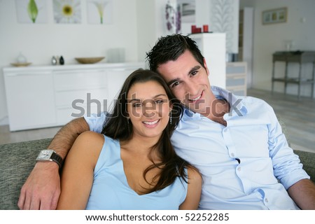 Portrait of a man and a woman smiling on a sofa