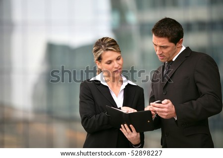 Portrait of a man and  awoman reading an agenda - stock photo