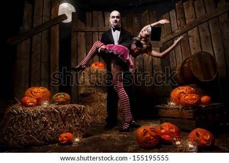Portrait of a man and sexy woman vampires with halloween pumpkin against wooden background. Shot in a studio. - stock photo