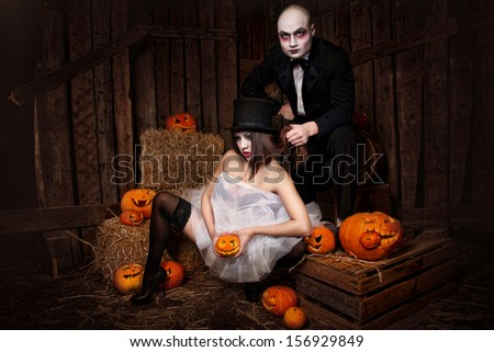 Portrait of a man and sexy woman vampires with halloween pumpkin against wooden background. Shot in a studio.