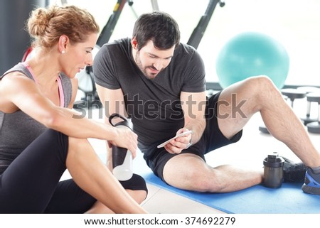 Portrait of a man and woman taking a break after a workout at the gym. Fitness trainer using applications on his mobile phone while sitting next to sporty woman and talking. - stock photo
