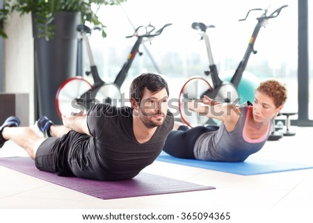 Portrait of a man and woman training together at the gym.