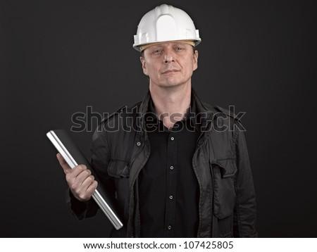 Portrait of a man architect on black background - stock photo