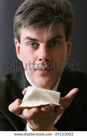 Portrait of a man blowing a kiss. Isolated against gray background - stock photo
