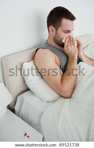 Portrait of a man blowing his nose in his bedroom - stock photo