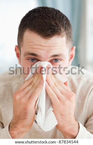 Portrait of a man blowing his nose in his living room - stock photo