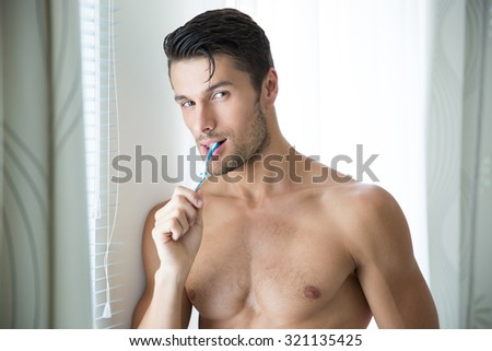 Portrait of a man brushing teeth and looking at camera - stock photo