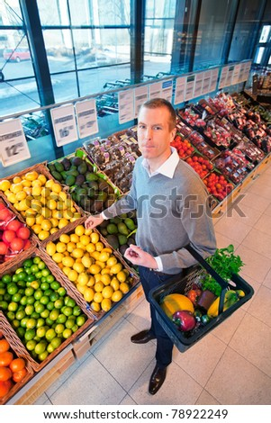 Portrait of a man buying fruits in the supermarket - stock photo