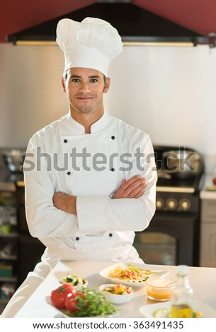Portrait of a man chef. He is looking at camera with confidence, facing a kitchen table with colorful dishes. He is wearing chef white clothes and hat, another woman chef is cooking behind him. - stock photo