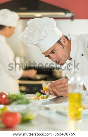 Portrait of a man chef in his forties. He is focused on putting sauce on a colorful plateful He is wearing white chef clothes and hat. Another woman chef is cooking in the blurred background. - stock photo