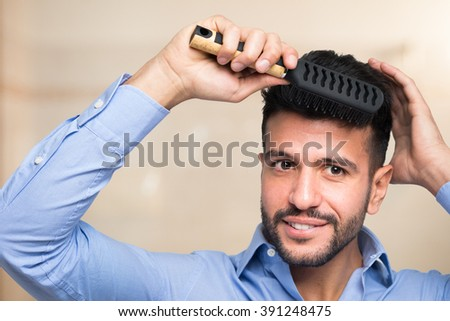Portrait of a man combing his hair