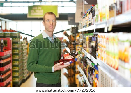 Portrait of a man comparing two products in a grocery store - stock photo
