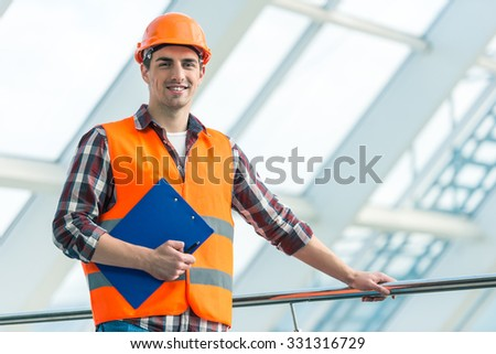 Portrait of a man construction builder in yellow helmet and vest the office center - stock photo