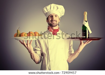 Portrait of a man cook holding a bottle of champagne and fruits. Shot in a studio over grey background. - stock photo