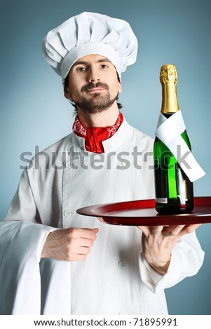 Portrait of a man cook holding a bottle of champagne. Shot in a studio over grey background. - stock photo