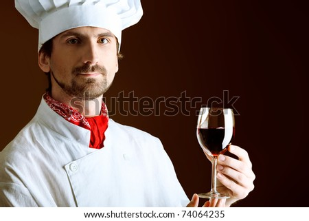 Portrait of a man cook holding a glass of red wine. Shot in a studio over black background. - stock photo