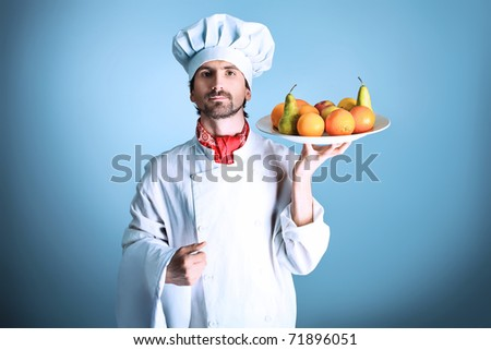 Portrait of a man cook holding a plate with fruits. Shot in a studio over grey background. - stock photo