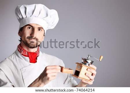Portrait of a man cook holding coffee grinder. Shot in a studio over grey background. - stock photo