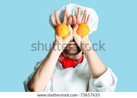 Portrait of a man cook holding oranges. Shot in a studio over grey background. - stock photo