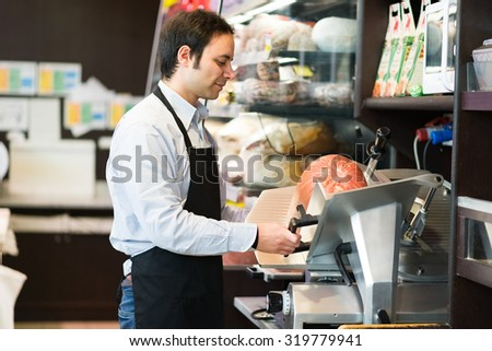 Portrait of a man cutting ham in a grocery store - stock photo