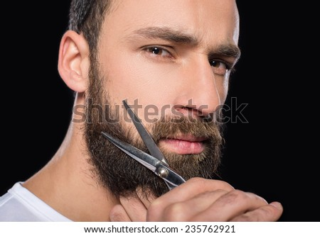 Portrait of a man cutting his beard with scissors.