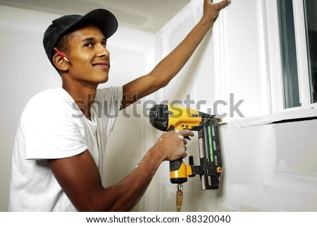 Portrait of a man drilling into a wall during renovations