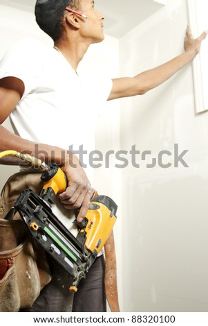 Portrait of a man drilling into a wall during renovations - stock photo