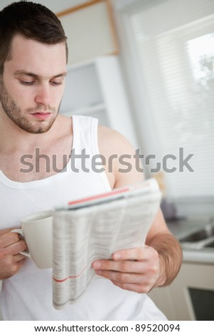Portrait of a man drinking orange juice while reading the news in his kitchen