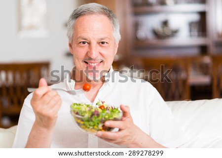 Portrait of a man eating a salad in his apartment - stock photo