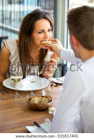 Portrait of a man feeding bread to his girlfriend - stock photo