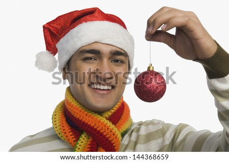 Portrait of a man holding a Christmas ornament