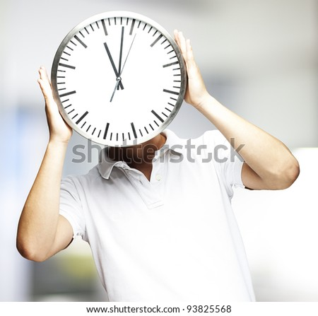 portrait of a man holding a clock indoor