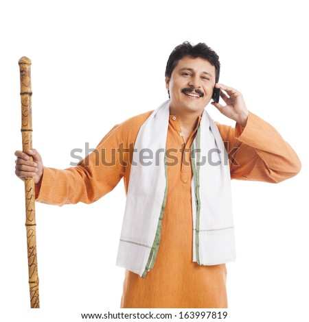 Portrait of a man holding a wooden staff and talking on a mobile phone - stock photo