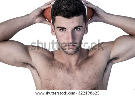 Portrait of a man holding ball over his head against white background - stock photo