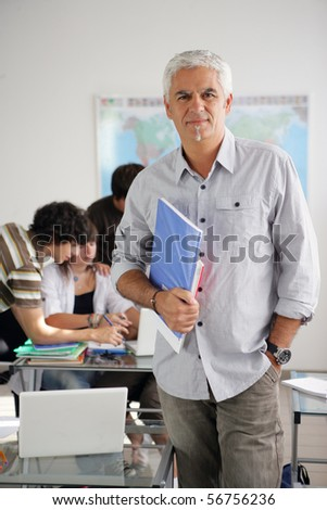 Portrait of a man holding documents in a classroom - stock photo