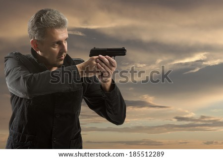 Portrait Of A Man Holding Gun against a sunset background - stock photo