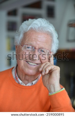 Portrait of a man holding one hand on his face and smiling in his house - stock photo