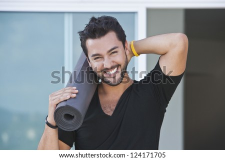 Portrait of a man holding yoga mat and smiling with his hand behind his head - stock photo