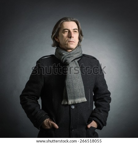 Portrait of a man in a black coat and a scarf around his neck. - stock photo