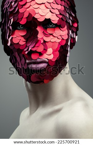 Portrait of a Man in a creative mask on gray background - stock photo