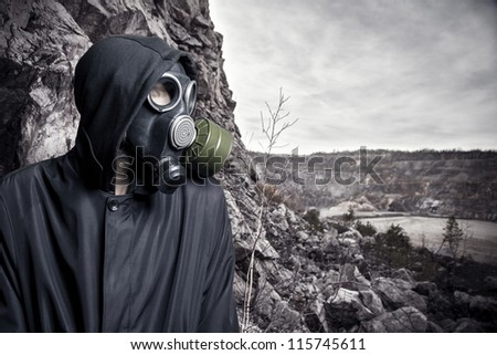 Portrait of a man in a gas mask and hood against the fading landscape - stock photo